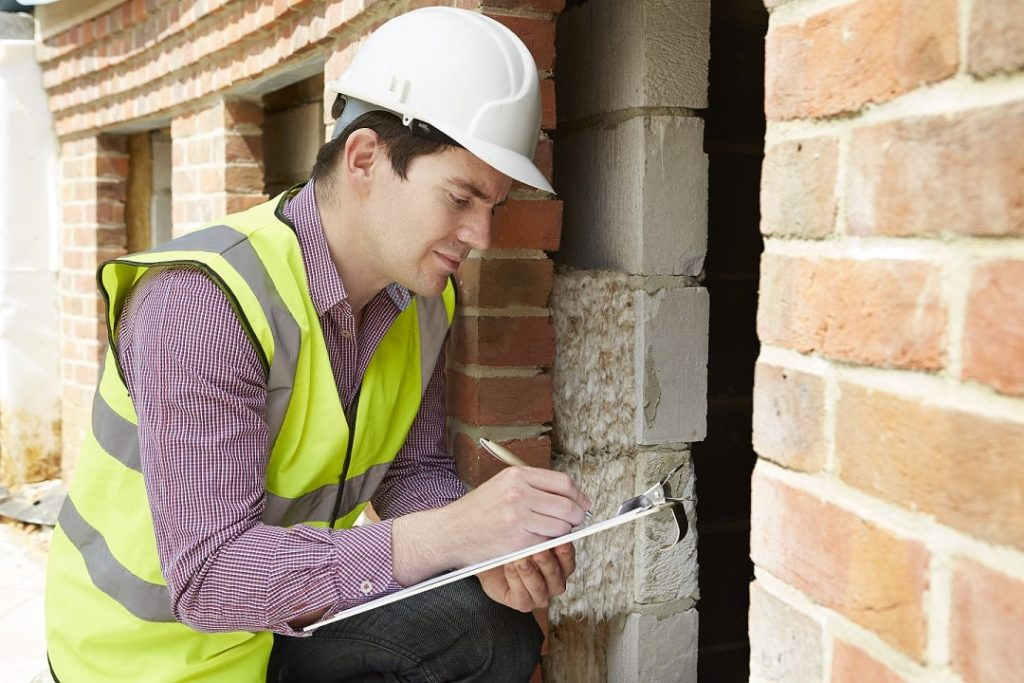 Home Inspector Checking Insulation During House Inspection